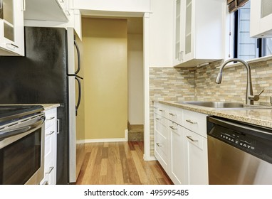 Modern white cabinets and brown mosaic back splash in apartment. Northwest, USA