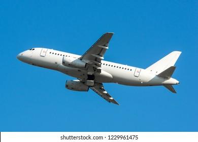 Modern white civilian airplane in the blue sky