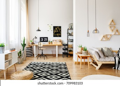 Modern white craft room in open apartment with creative design, triangle shelves, industrial pendant lamps, wooden furniture, patterned rug, hardwood floor, sofa and desk
