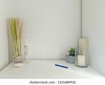 modern white desk interior design with decoration elements, copy space for pictures, images, canvas or photos and white wall in the background