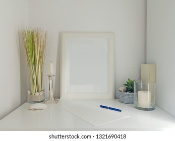 modern white desk interior design with decoration elements, frame for pictures and white wall in the background