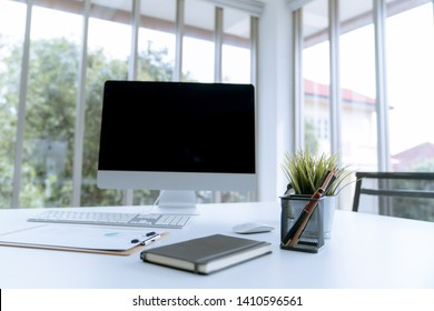 Modern white desk work table with computer laptop and stationary in home office