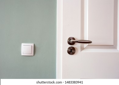 Modern white door with chrome door handle and light switch, new clean design retro