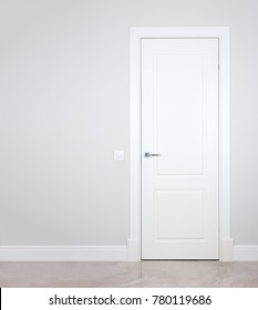 Modern white door. Grey wall with free space. Minimalist bright interior