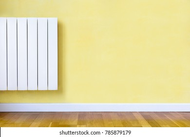 Modern white electric heater with electronic thermostat fitted in a room with yellow wall, wooden floor and white baseboard.