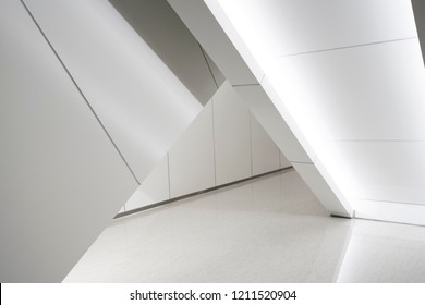 Modern white futuristic scene visual element interior design. Triangle shape void with lighting decoration underneath escalator in modern interior space