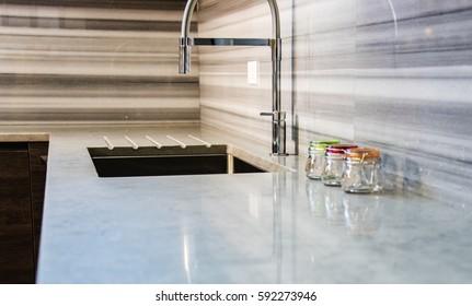 Modern white and gray kitchen countertop with full granite backsplash.
