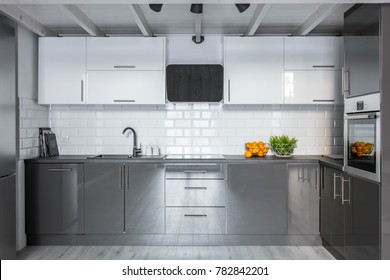 Modern white and gray kitchenette with ceramic brick tiles