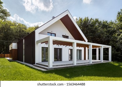 Modern white house in white with wooden elements and garden with green lawn