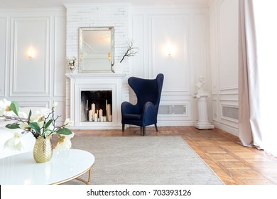 Modern white interior design in classical style of a spacious studio apartment with a huge bed, a wooden large shelf and a beautiful white sofa