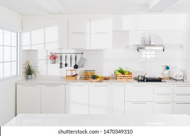 Modern white kitchen with counter and white details, minimalist interior with sunlight in daytime. Full set of kitchen equipment, pan, pot, electric hob, flipper, vegetable, fruit.