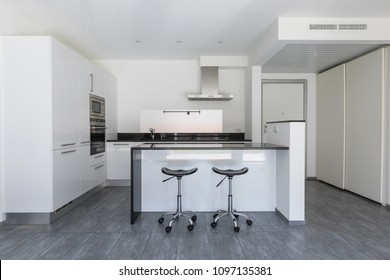 Modern white kitchen with island and stools. Nobody inside