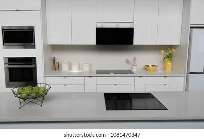 Modern white kitchen with quartz countertop, island, stainless c