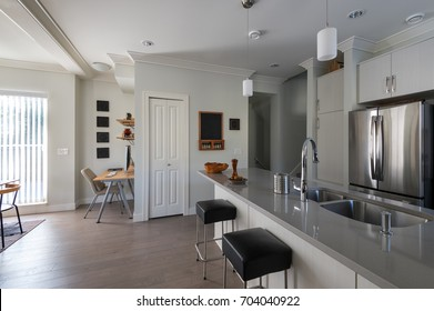 Modern white kitchen with stainless steel appliances and small office. Interior design.
