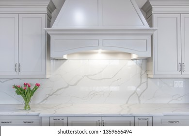 A modern white kitchen with a traditional touch. White marble-looking quartz countertop and backsplash accompanied by white cabinetry and custom made range hood.