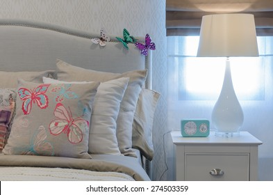 modern white lamp and retro clock on table in bedroom at home