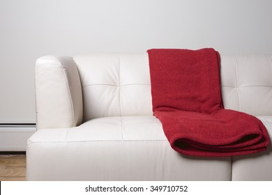 Modern white leather sofa with red blanks.