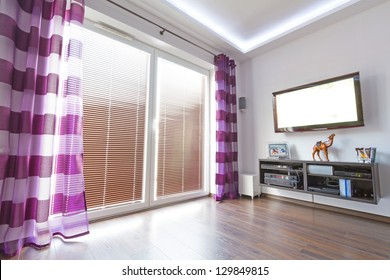 Modern white living room interior with purple curtains