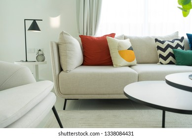 Modern white living room interior with red,yellow and green pillows on it. Minimal interior style.