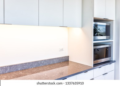 Modern white minimalist kitchen features cabinets with granite countertop and microwave toaster with empty space in office or home
