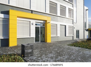 modern white office building with yellow entrance