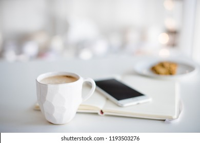 Modern white office, designer handmade cup of coffee, smartphone