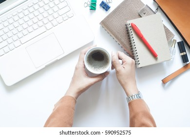 Modern white office desk with businesswoman holding cup of coffee, Flat lay