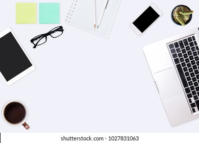 Modern white office desk table with laptop computer, smartphone, notebook, pen, pencil, and cup of coffee. Working desk table concept.Top view with copy space, flat lay.