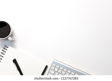 Modern white office desk table with keyboard computer, coffee, pen and notebook paper with workspace top view workspace.