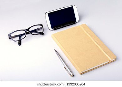 Modern white office desk table with laptop, smartphone and other supplies. Blank notebook page for input the text in the middle. Top view.
