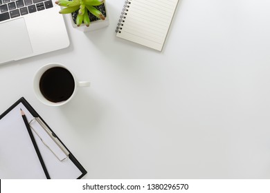 Modern white office desk table with laptop computer, notebook and coffee cup.Top view with copy space, flat lay.