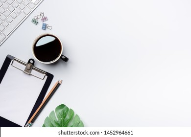Modern white office desk table with keyboard, and other supplies with cup of coffee. Blank notebook page for input the text in the middle. Top view, flat lay.