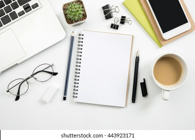 Modern white office desk table with laptop, smartphone and other supplies with cup of coffee. Blank notebook page for input the text in the middle. Top view, flat lay.