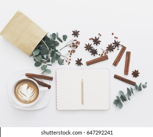 Modern white office desk table with cup of coffee. Blank notebook page for input the text in the middle. Morning composition. Top view, flat lay.