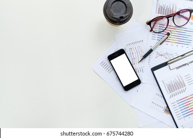 Modern white Office desk table with  blank screen smart phone,pen,financial report and cup of coffee .Top view with copy space.Business analysis and strategy concept.