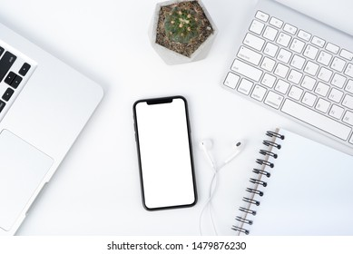 Modern white office work table with smartphone mock up laptop ,earphone and catus, top view