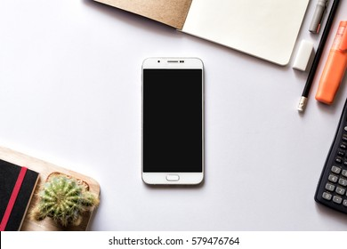 Modern white office work table with smartphone mock up notebook pen and calculator top view