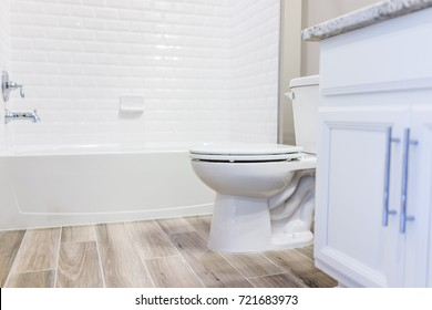Modern white plain clean toilet bathroom, bathtub with shower tiles and hardwood floors with staging in model staging house, home or apartment