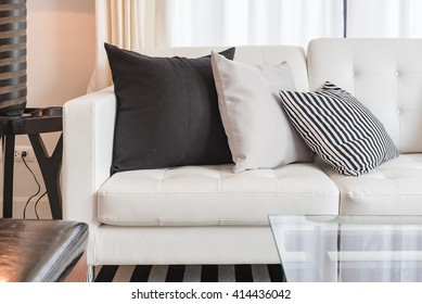 modern white sofa with brown pillows in living room design