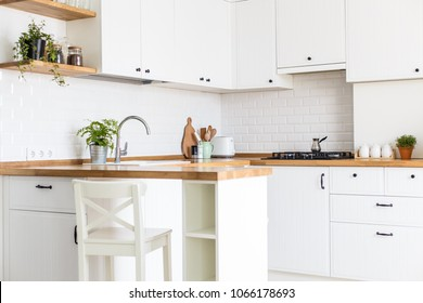 Modern white u-shaped kitchen in scandinavian style. Open shelves in the kitchen with plants and jars