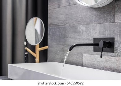 Modern white washbasin with black tap mounted to wall
