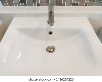 Modern white washbasin with metal tap in bathroom, top view