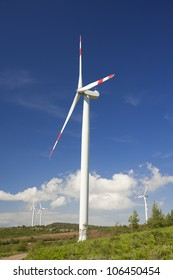 modern white wind turbine with blue sky