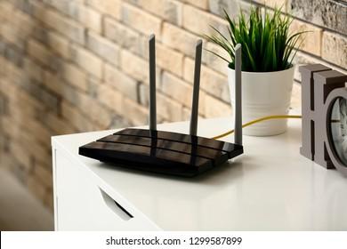 Moderner Wi-Fi-Router auf hellem Kommode bei Ziegelwand