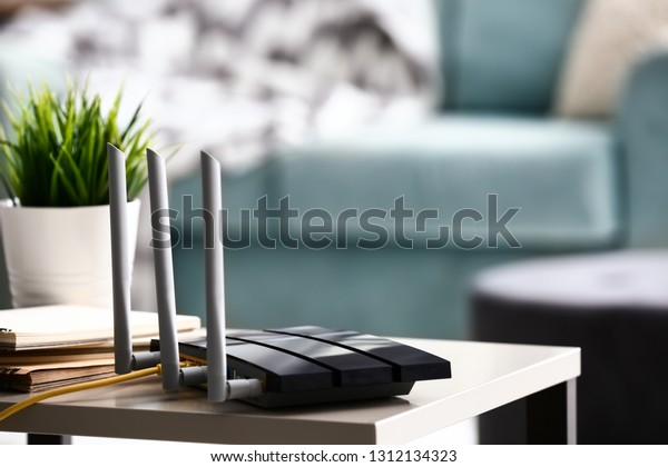 Modern wi-fi router on light table in room