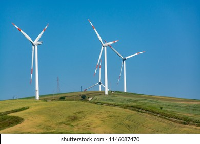 Modern wind farm with big wind turbines towers, source for renewable green energy