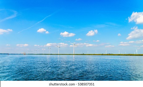 A Modern Wind Farm consisting of Wind Turbines with Two and Three Blades along the Shore of Veluwemeer under Partly Cloudy and Blue Sky in the Netherlands