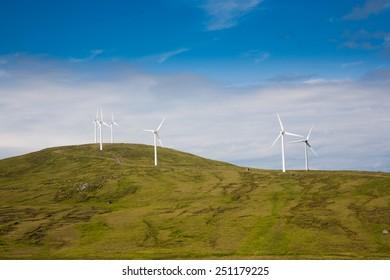 Modern windmills on a green hill