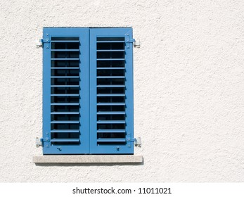Modern window with closed blue shutters in white rendered wall