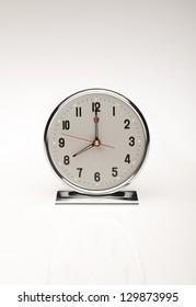 Modern wind-up clock on white background.